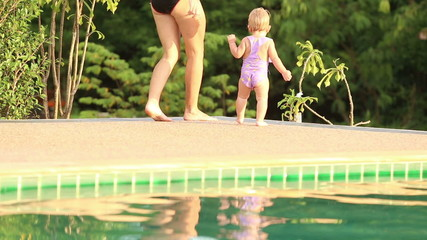 one year baby girl runs near the swimming pool