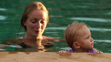 mother and douther swim in the pool