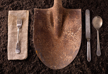 Rusted shovel on soil background with fork, knife, spoon, and na