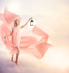 Young woman on fantasy clouds with antique lamp