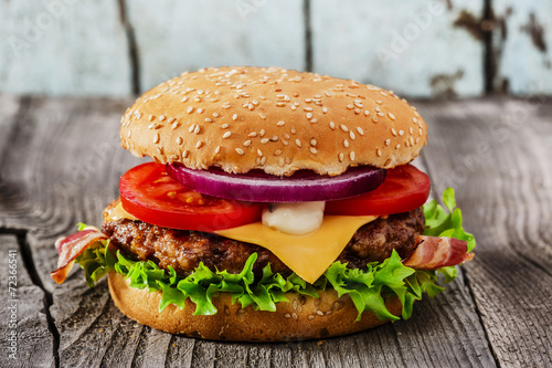 Poster Voorgerecht hamburger with grilled meat cheese bacon on a wooden surface