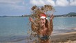 Uplifting Motivational Celebration of Girl on Beach in Santa Hat