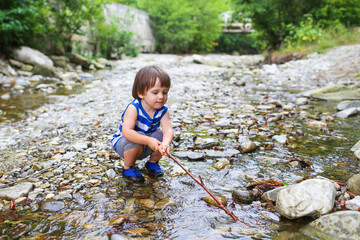 toddler boy plays with stick in flashy river