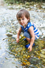 toddler boy plays in flashy river