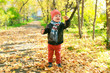 Happy little child plays with leaves in autumn outdoors