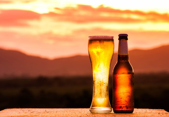 Bottle and Glass of light beer on sunset