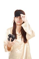 Sleepy Asian girl pull eye mask look at  alarm clock