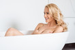 Laughing blond woman posing nude in a bath