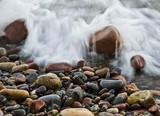 rocas en la playa mojandose por un ola - 72372383