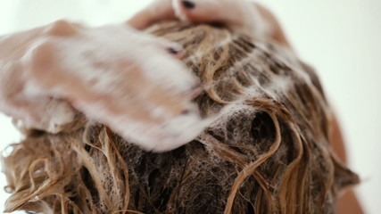 Close up of a woman showering and washing her hair with shampoo