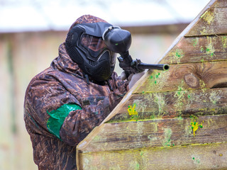 Man with paintball gun behind fortification with paint splashes