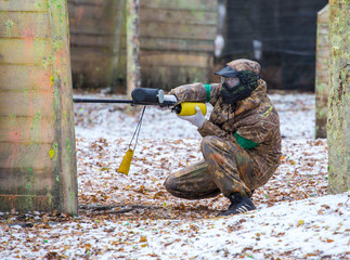 Extreme playing paintball on first snow outdoors