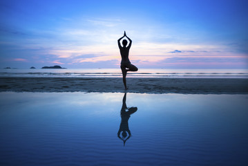 Woman practicing yoga on beach at sunset.