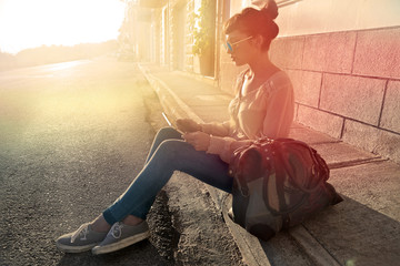 Girl sitting in the sun and using a tablet