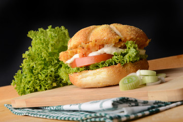 Appetizing fish burger with leek on wooden board
