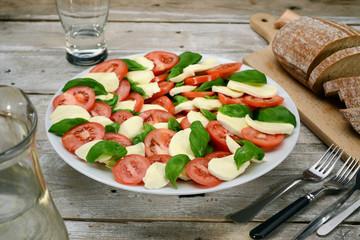 Caprese salad on white plate & vintage wooden desk
