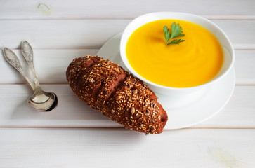 Pumpkin soup on a wooden table with a spoon