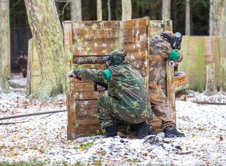 Two paintball shooters defending the fortification on snow
