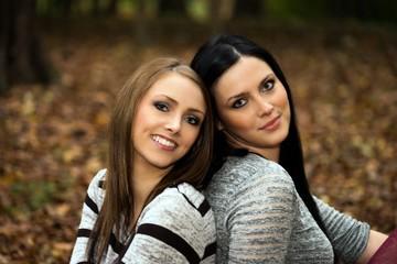 zwei Frauen sitzen in einem herbstlichen Wald