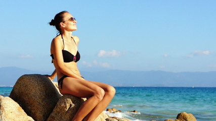 Young woman sitting on a beach and enjoying the sun
