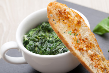 Sauteed garlic spinach dish, baked bread slice  with  melted che