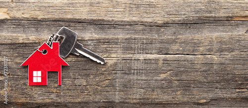 Leinwandbild Motiv Symbol of the house with silver key on vintage wooden background