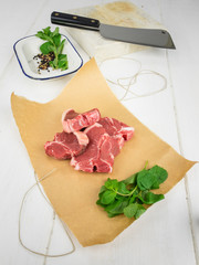 lamb chops with mint on brown paper with  utensils behind