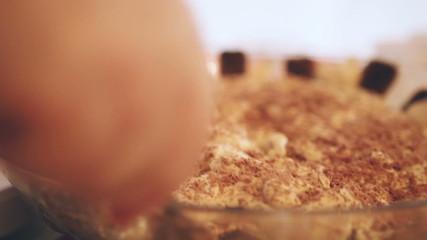 Tiramisu casserole with hand slicing pieces for serving