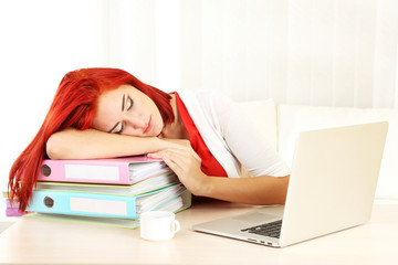 Tired girl with notebook sleeps on table