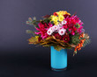 Flower bouquet in blue vase on dark grey background