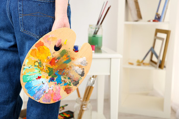 Artist holding palette with paints in art studio