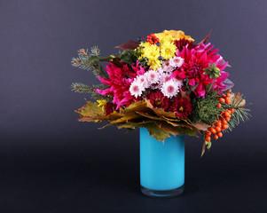 Flower bouquet in blue vase on dark grey background