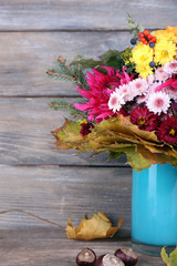 Flower bouquet in blue vase on grey wooden background