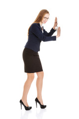 Businesswoman trying to push the wall