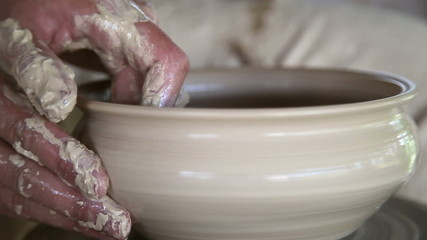 potter sculpts clay small pot 3
