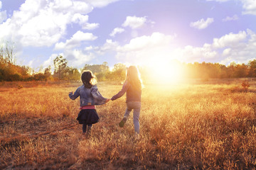Two young girls runs on the sunny meadow