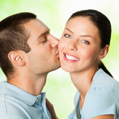 Happy young couple kissing, outdoor