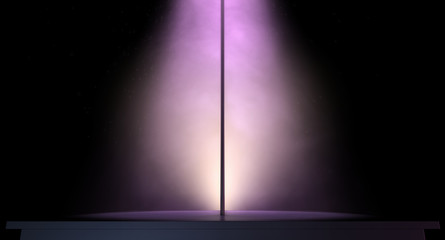 stripper pole on a stage lit by a single spotlight