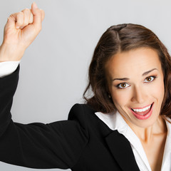 Happy gesturing business woman, over grey
