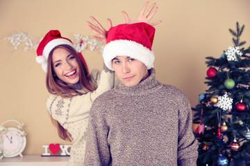 Nice love couple near Christmas tree. Woman and man celebrating