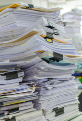 Pile of documents on desk stack up high waiting to be managed