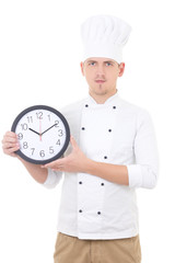 young man chef in uniform showing office clock isolated on white