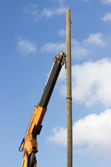 Crane hook lifting the wooden telephone pole out