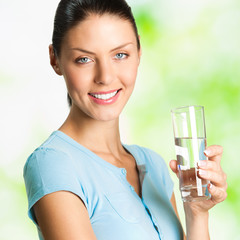 Young smiling woman with glass of water, outdoor
