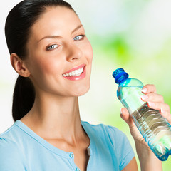 Young woman with bottle of water, outdoor