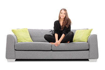 Young woman sitting on a sofa and looking in the camera