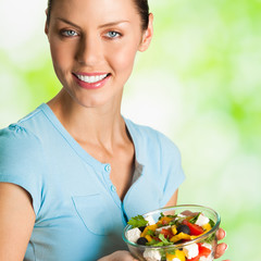 Smiling woman with salad, outdoors