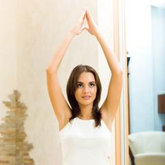 Young happy woman doing yoga exercise