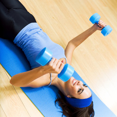 Young woman with dumbbells at home