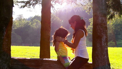 Mother and daughter hugging and kissing on tree log in Sunset
